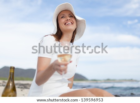 Young woman having picnic on the beach - stock photo