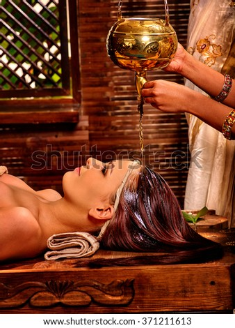 Young woman having pouring oil lamp Ayurveda spa treatment. - stock photo
