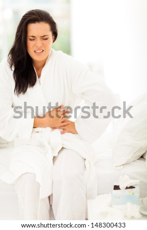 young woman having stomach pain at home - stock photo