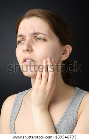 Young woman having toothache - stock photo