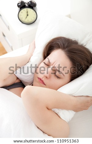 Young woman having trouble with getting up early in the morning, shallow depth of field, focus on foreground - stock photo