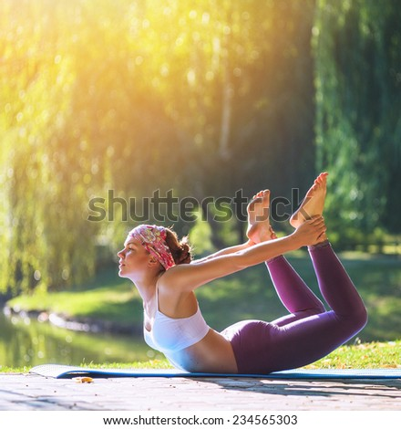 Young woman having yoga practicing in morning park near lake  - stock photo