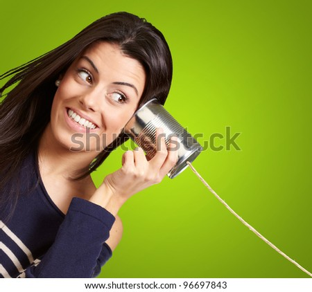 Young woman hearing using a metal tin can over green background - stock photo