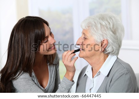 Young woman helping old woman to put makeup on - stock photo