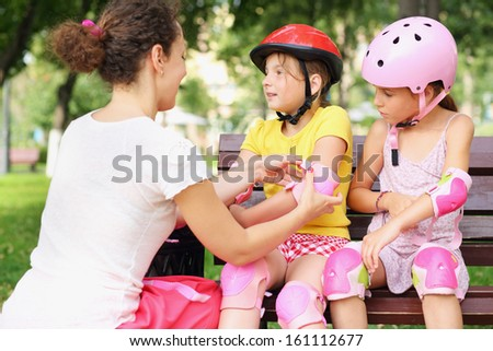 Young woman helping to put on elbow pads two girls in a park - stock photo