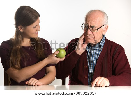 young woman helps senior man to eat green apple - stock photo