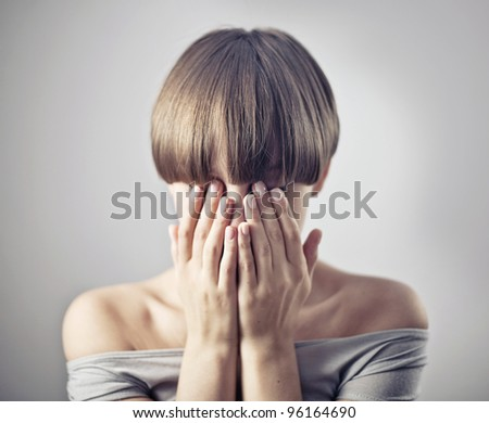 young woman, hide her face in her hands - stock photo