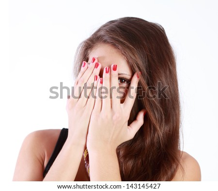 Young woman hides her face in her palms and spies isolated on white background. - stock photo