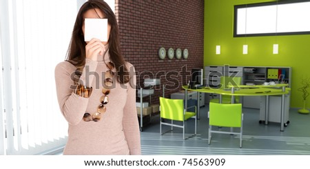 Young woman hiding her face with a blank message in a office - stock photo