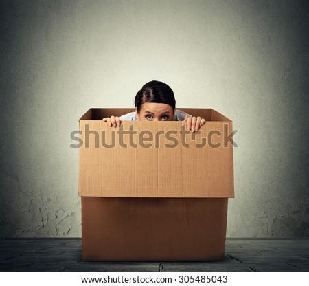 Young woman hiding in a carton box - stock photo