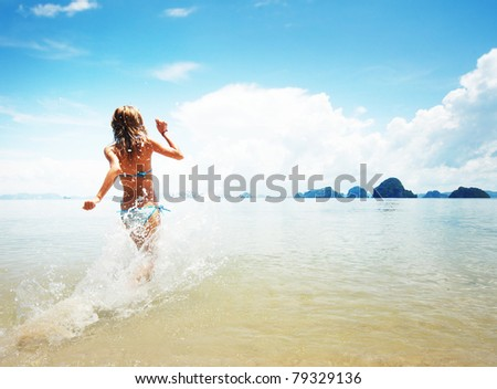 Young woman hight speed running into sea with splashes - stock photo