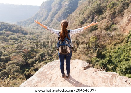 young woman hiker arms open on mountain cliff - stock photo