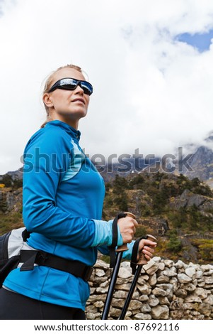 Young woman hiker hiking in mountains in Nepal - stock photo