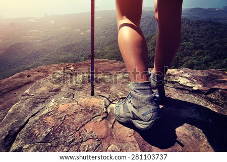 young woman hiker legs on mountain peak cliff - stock photo