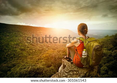 Young woman hiker sits on the edge of the cliff and enjoying sunrise looking at the valley and mountains. Traveling along Asia, active lifestyle concept  - stock photo