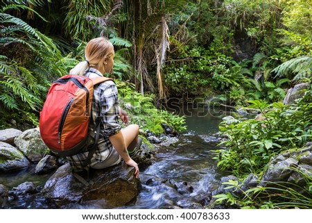 Young woman hiker sitting on rocks in stream - stock photo