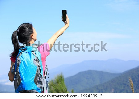 young woman hiker use smart phone taking self photo at mountain peak  - stock photo