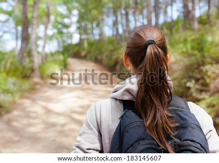 Young woman hiker walking on a rural road through the forest. - stock photo
