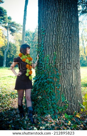 Young woman hiking in autumn park dressed in knitted dress and scarf. - stock photo