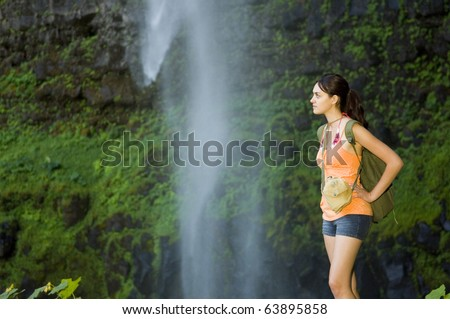 Young woman hiking in summer near waterfall. - stock photo