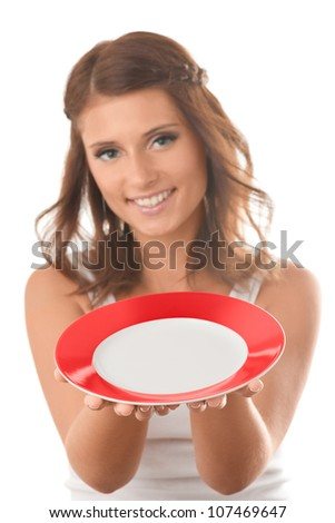 Young woman hold out a plate. You can put anything on the plate that you want - stock photo