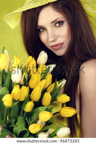 Young  woman hold yellow tulips flower on green - stock photo