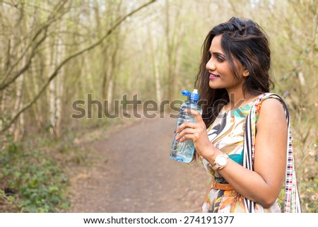 young woman holding a bottle of water - stock photo