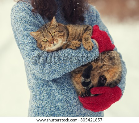 Young woman holding a cat outdoors in winter - stock photo