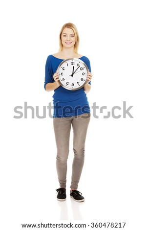 Young woman holding a clock. - stock photo