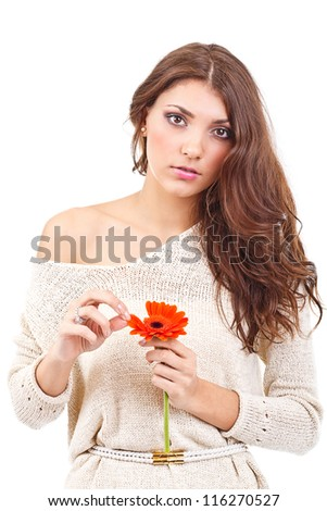 Young woman holding a flower and tearing petals - stock photo
