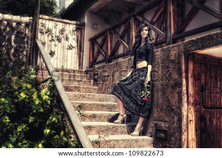 Young woman holding a flower whilst standing on stairs. - stock photo