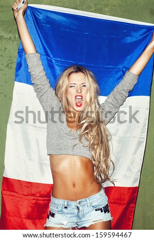Young woman holding a french flag against a green wall background. Lifestyle. - stock photo