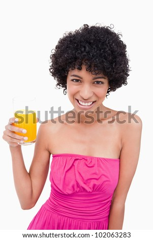 Young woman holding a glass of orange juice while smiling - stock photo