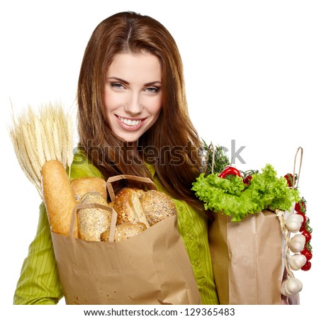 Young woman holding a grocery bag full of fresh and healthy food - stock photo