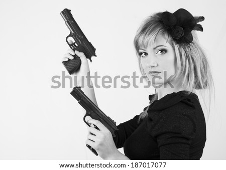 Young woman holding a gun on white background ( black and white ) - stock photo