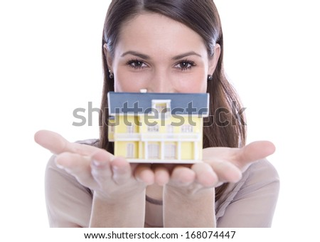 Young woman holding a house in her hands. Isolated on white. - stock photo