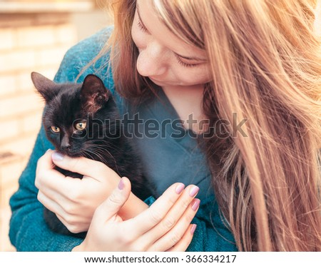 Young woman holding a kitten - stock photo