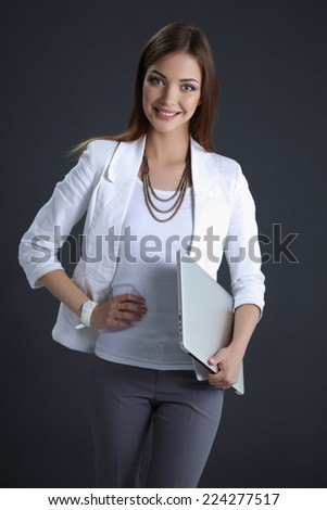 Young woman holding a laptop, isolated on grey background - stock photo