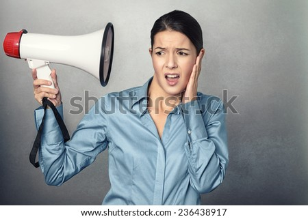 Young woman holding a megaphone to her head and clutching her ear with an aggrieved expression at the loudness of the sound so close to her, conceptual image isolated on grey - stock photo