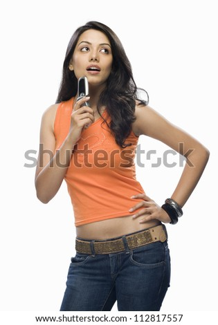 Young woman holding a mobile phone and thinking - stock photo