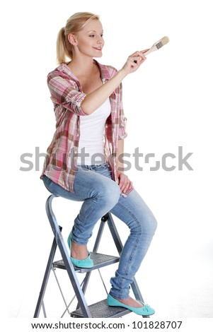 Young woman holding a paintbrush  isolated on white background - stock photo