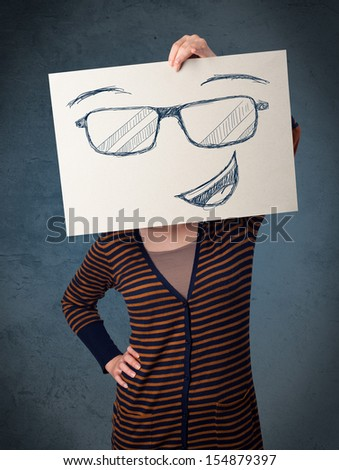 Young woman holding a paper with a smiley face on it in front of her head - stock photo