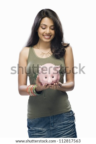 Young woman holding a piggy bank - stock photo