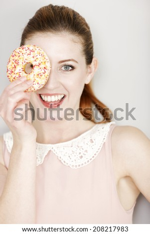 Young woman holding a ring doughnut over her eye smiling. - stock photo