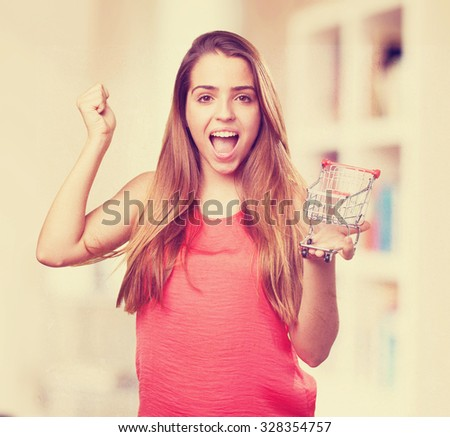 young woman holding a shopping cart doing a winner gesture - stock photo