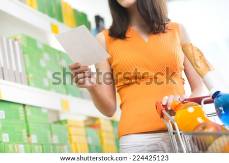 Young woman holding a shopping list an searching products on shelves. - stock photo