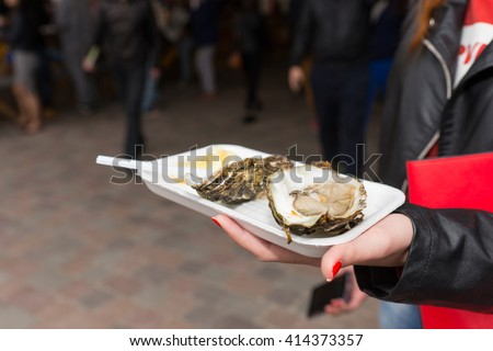 Young woman holding a single fresh opened oyster with lemon garnish on a takeaway tray at an evening market, close up view - stock photo