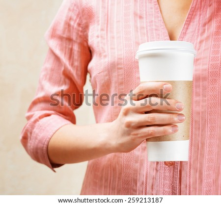 Young woman holding a tumbler of coffee in cafe, drinking and enjoying the aroma of coffee. Woman in fashionable pink blouse. - stock photo