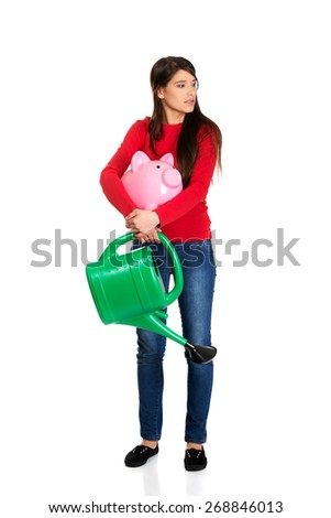 Young woman holding a watering can and piggybank. - stock photo