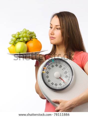 Young woman holding a weight scale and plate with fresh fruit - stock photo